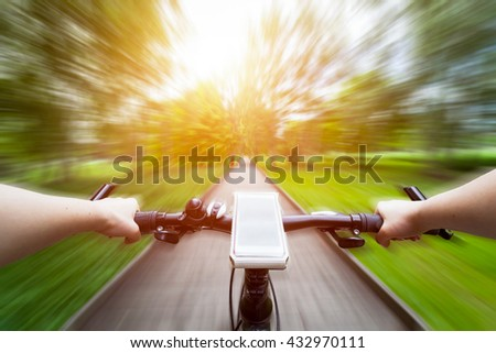 Riding a bike first person perspective. Smartphone attached to handlebar. Speed motion blur. Countryside road towards sun.