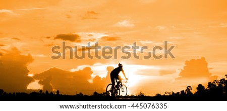 Riding a bike  in the evening for exercise ,as silhouette style - stock photo