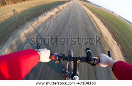 Riding a mountain bicycle on a country road (motion blurred image) - stock photo