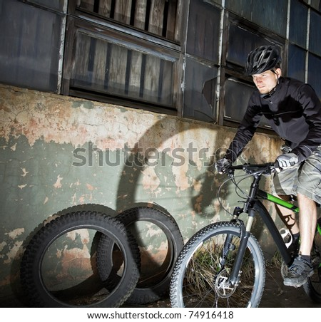 Riding bicycle in industrial environment, urban mountain biking - stock photo