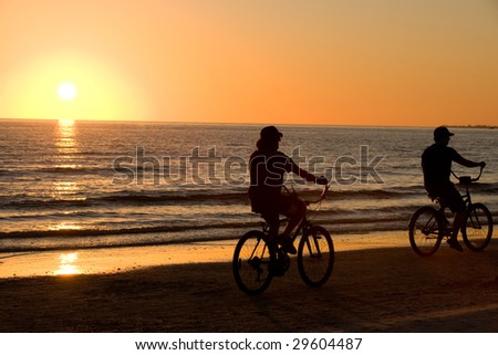 Riding bike on Floridian Fort Meyers beach in sunset - stock photo