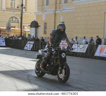 Riding biker standing with smoke from under the wheels. St. Petersburg, Russia - 12 August, 2016. The annual International Festival of Motor Harley Davidson in St. Petersburg Ostrovsky Square.