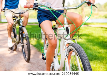 Riding bikes in park. Close-up of couple riding bicycles in park together  - stock photo