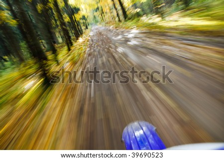 Riding dirtbike on country road in autumn scene, motion blur from drivers point of view - stock photo