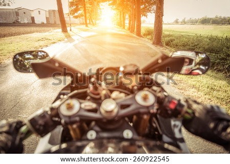 riding fast on the country side area. motorcycle rearing during full acceleration - stock photo