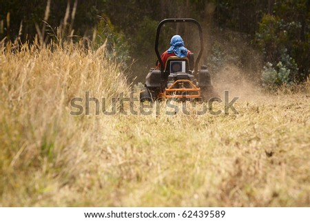Riding lawn mower blowing grass - stock photo
