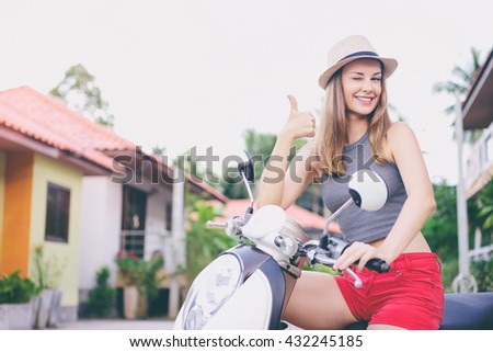 Riding lifestyle. Outdoor portrait of pretty young woman in hat sitting on scooter showing thumb up. - stock photo
