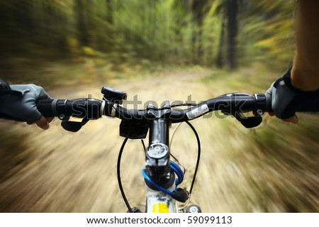 Riding on a bike in forest's path - stock photo
