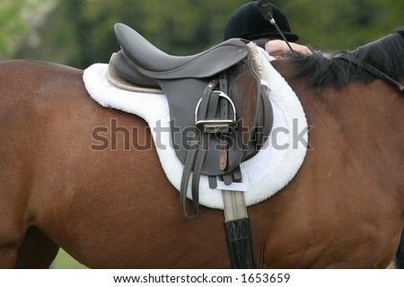 Riding Saddle on a chestnut colored horse, rider in background with helmet on. - stock photo