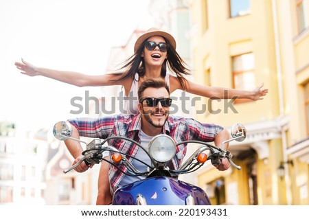 Riding scooter together. Beautiful young couple riding scooter together while happy woman keeping arms outstretched and smiling  - stock photo
