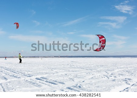 riding the kite on the ice of big lake - stock photo