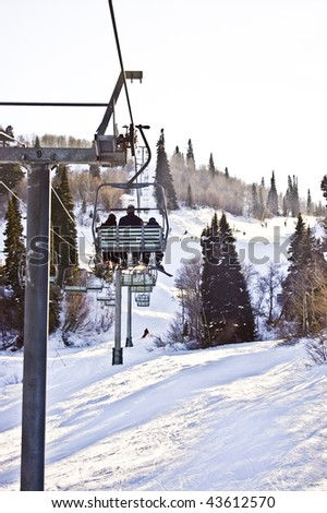 Riding to the top of the Snow Basin on a Ski Lift over looking the trail and skiers below - stock photo