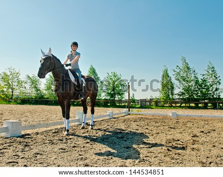 riding young woman on horse in outdoor with sky background - stock photo