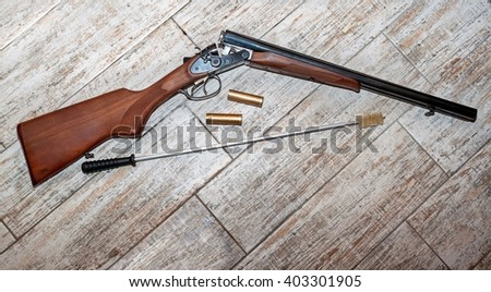 Rifle and bullets with cleaning supplies on rustic wooden background - stock photo