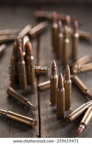 Rifle bullets on wood table with low key scene