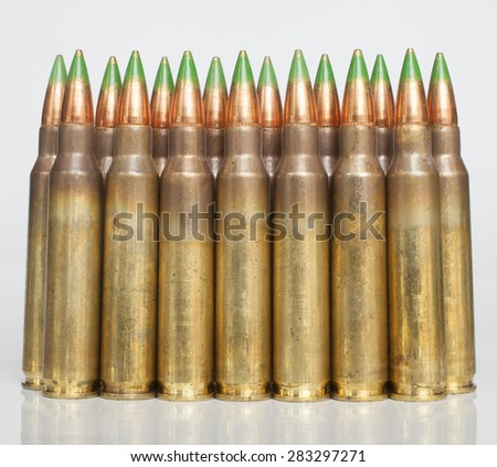 Rifle cartridges with bullets that have a green tip on a white background - stock photo