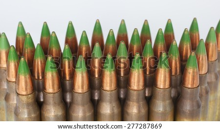 Rifle cartridges with green tipped bullets on a white background - stock photo