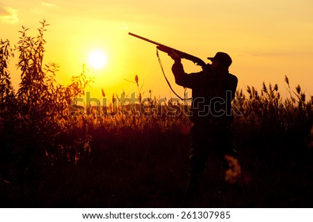 Rifle Hunter Silhouetted in Beautiful Sunset. Summer. - stock photo