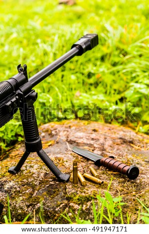 Rifle standing on a bipod and combat knife with empty shells on a rock in the grass after a rain. Close up view of a stone level