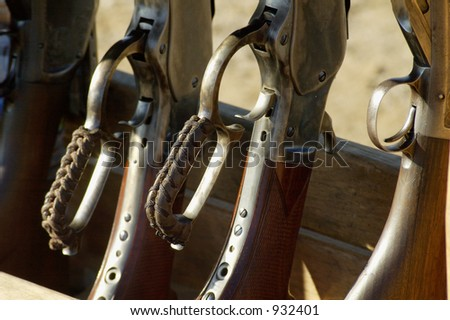Rifles and shotguns at a cowboy shoot competition.