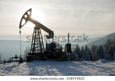 Rig for extraction oil , on  snow in the mountains  - stock photo