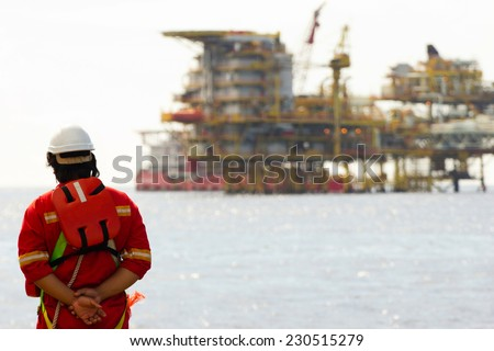 Rig workers and an oil platform - stock photo