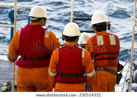 Rig workers using a swing rope prior of being transported to nearby rigs by boat  - stock photo