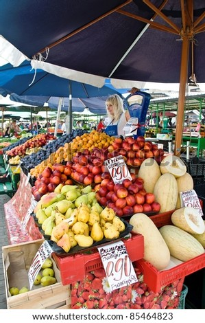 RIGA, LATVIA - AUGUST 3: An unidentfied fruit seller works at the Riga Central market on August 3, 2011 in Riga, Latvia. The market is considered to be the oldest and biggest market in Europe. It opened on November 2, 1930 and is 72.3 thousand square mete - stock photo