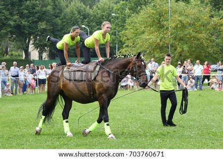 RIGA, LATVIA - AUGUST 19, 2017: Equestrian club members show performance of vaulting on horseback within city day on August 19, 2017 in Riga, Latvia. The city day celebration is held annually.