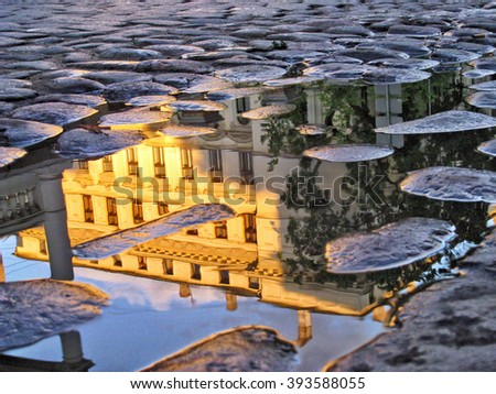 Riga Latvia capital city reflecting in a puddle on cobblestone street after the rain during golden hour before sunset - stock photo