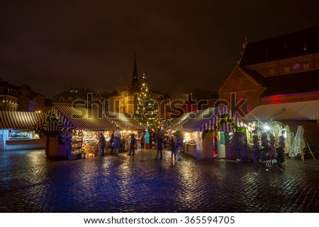 RIGA, LATVIA - DECEMBER 20, 2015: People visit Christmas Fair in old town at evening on December 20, 2015 in Riga, Latvia