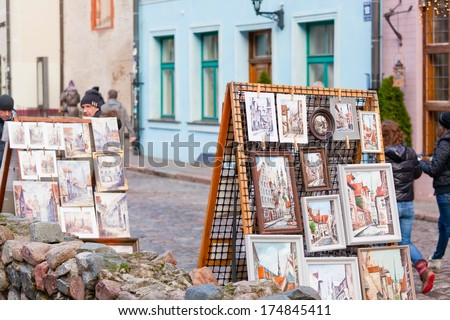 RIGA, LATVIA - DECEMBER 30, 2013: Pictures of sidewalk artists. Threshing barn capital of Latvia and the largest city of the countries of Baltic with population of 695 539 people