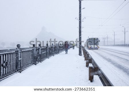 RIGA, LATVIA - DECEMBER 25, 2014: Unidentified Pedestrians and Bus with text RIGA on Stone bridge during heavy snow storm. - stock photo
