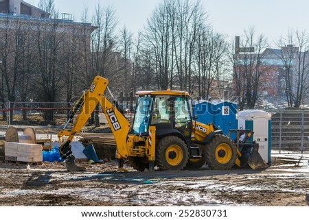 RIGA, LATVIA - FEBRUARY 15, 2015: Wheel loader excavator stays at construction site in Riga - stock photo