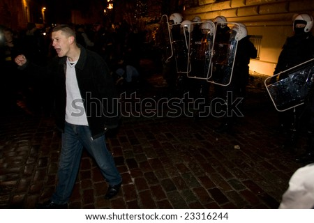 RIGA, LATVIA, JANUARY 13, 2009: After peaceful protest to call for early elections many anti-government demonstrators tried to break into parliament. Aggressive crowd and police had fight in downtown. - stock photo