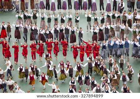 RIGA, LATVIA - JULY 11, 2015: Dancers in traditional costumes perform at the Grand Folk dance concert of Latvian Youth Song and Dance Festival in the Daugava Stadium. - stock photo