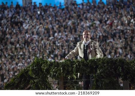 "RIGA, LATVIA - July 7, 2013: The Latvian National Song and Dance Festival Grand Finale concert ""Ligo!"". Conductor Maris Sirmais. Low light photo some digital noise present - stock photo"