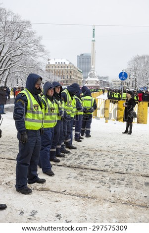 RIGA, LATVIA, MARCH 16, 2010: Local police guard cordon behind crowd control barriers at the Freedom Monument at the commemoration of the Latvian Waffen SS unit. - stock photo
