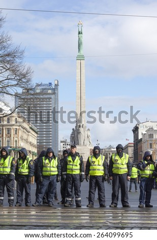 RIGA, LATVIA - MARCH 16, 2014:Police line infront of Freedom Monument ready to prevent provocations at Commemoration of Latvian Legion(WaffenSS). Event is drawing crowds of nationalists & antifascists - stock photo