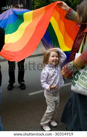 RIGA, LATVIA, MAY 16: Gay men and women and their supporters at parade in the Latvian capital, accompanied by a strong police presence and loud protest from anti-gay activists  in Riga, Latvia on May 16, 2009 - stock photo