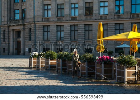 RIGA, LATVIA - 07 MAY 2016: Man cleans pavement around outdoor cafe.