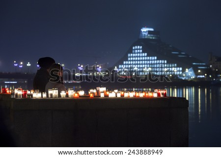 RIGA, LATVIA - NOVEMBER 11: Unidentified couple at commemoration of Soldiers Memorial Day. People light candles to honor victory over Russian German militia - keypoint in birth of Republic of Latvia - stock photo