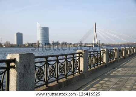 Riga, Latvia. Quay of the river Dvina and a kind on the bridge and high-rise buildings. - stock photo