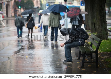 Riga, Latvia - September 12, 2012: A poor depressive person shoe gazing in the rainy streets of Riga.