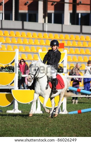 RIGA, LATVIA - SEPTEMBER 25 : An unidentified child on pony show jumps during Latvian Equestrian Federation cup in pony riding on September 25, 2011 in Riga, Latvia.