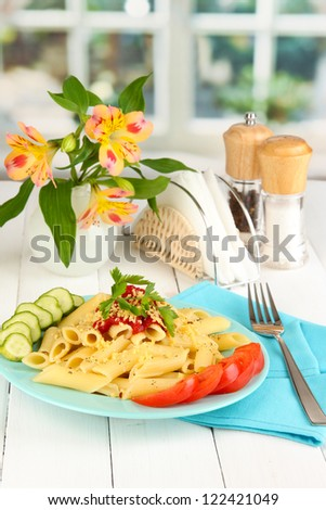 Rigatoni pasta dish with tomato sauce on white wooden table in cafe