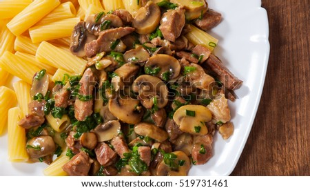rigatoni pasta with meat and mushroom sauce in a plate on wooden table