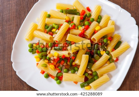 rigatoni pasta with mixed vegetables on white plate - stock photo
