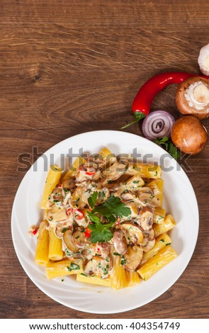 rigatoni pasta with mushroom sauce in a plate on wooden table - stock photo
