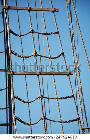 rigging ropes at the old sailing vessel against blue sky - stock photo